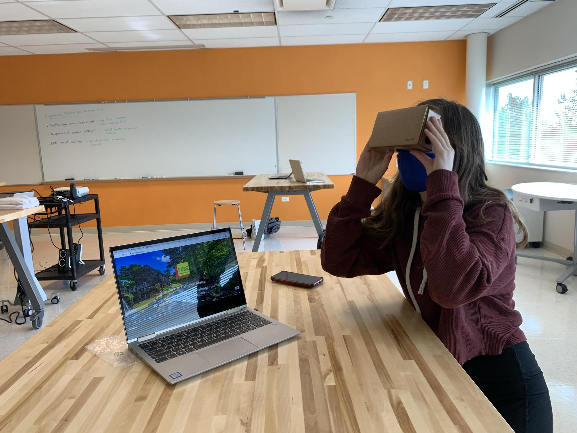student in classroom looking through prism