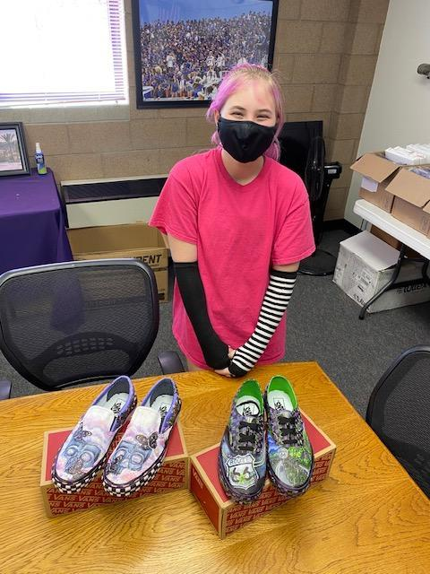 Student standing in front of shoes decorated with colorful drawings