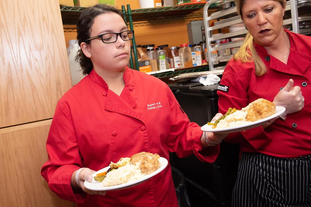 A student carries two plates of chicken cordon bleu and vegetables out of the Connolly Center kitchen as Chef Carolynn Parmenter looks on