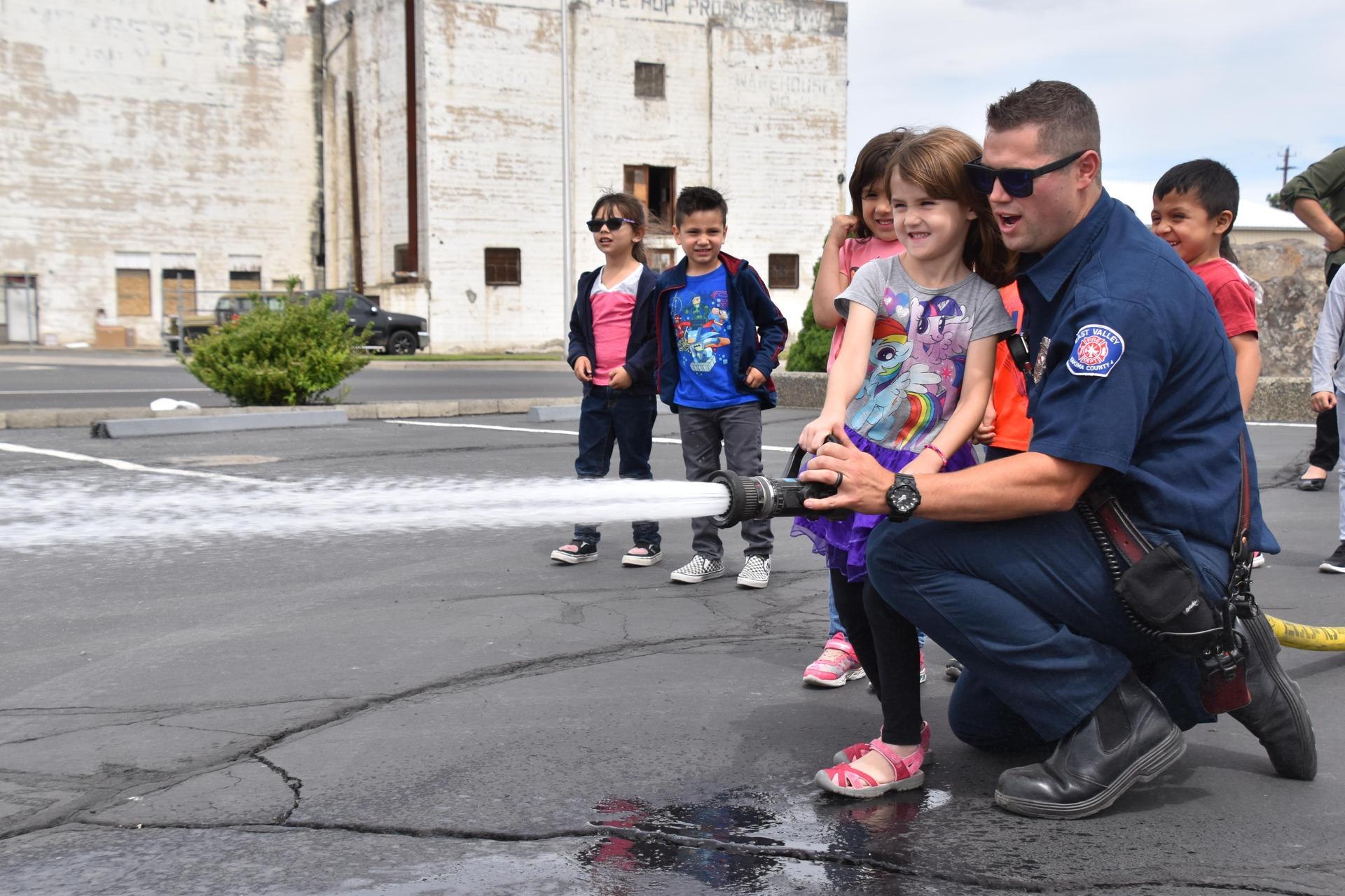 Girl spraying the fire house with the help of a Moxee firefighter.