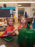 two girls smiling while painting a green pumpkin