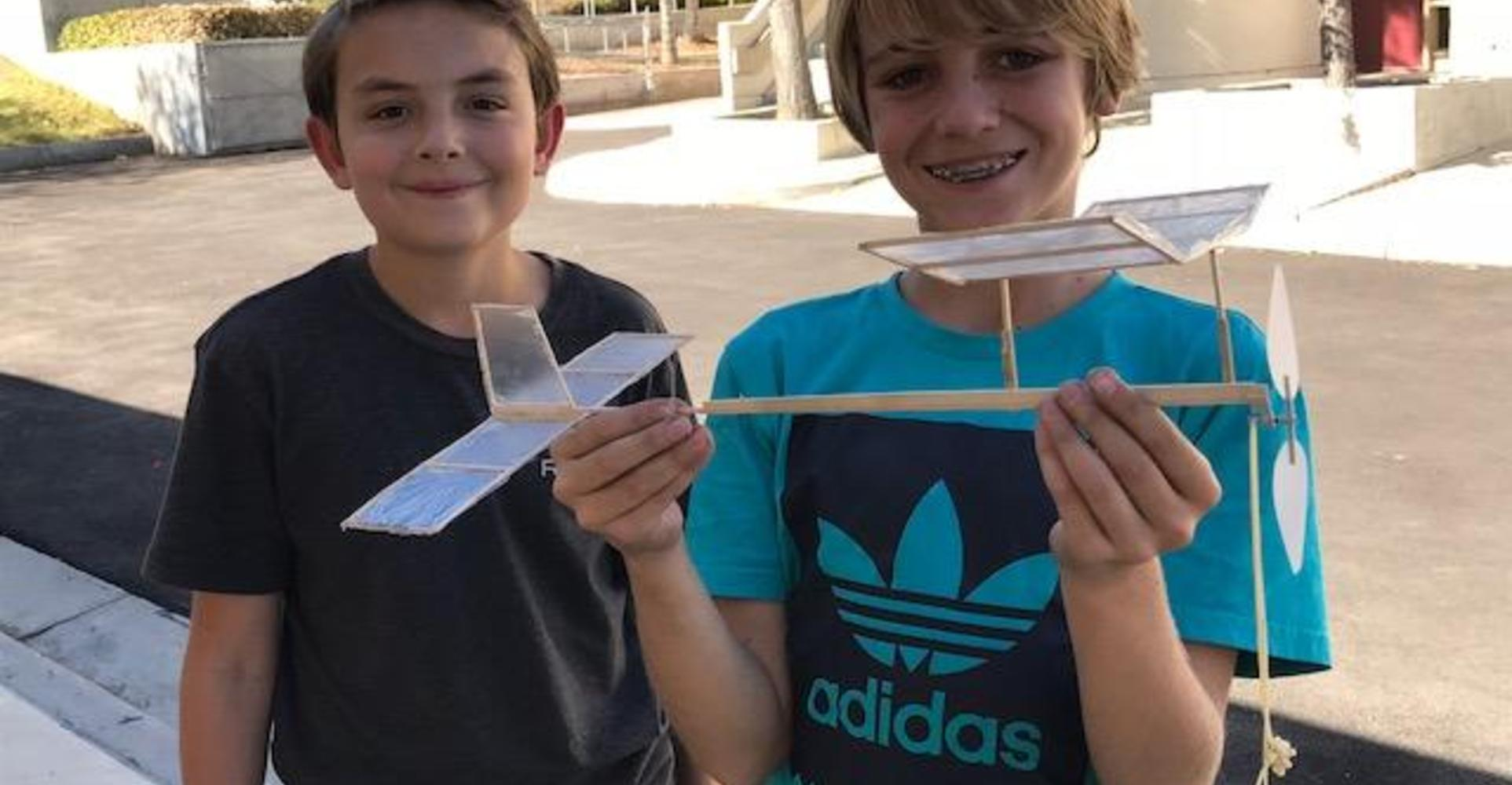 Students holding plane they built.