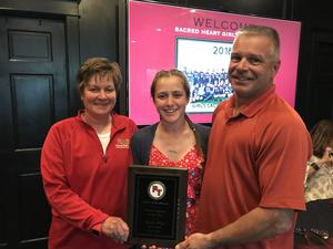 Kayla and parents with award