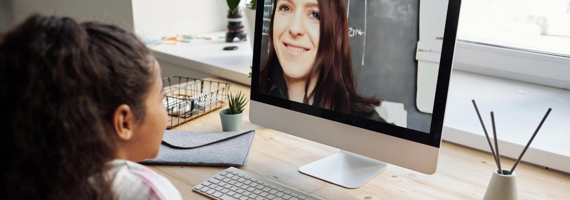 girl smiling at woman on computer monitor