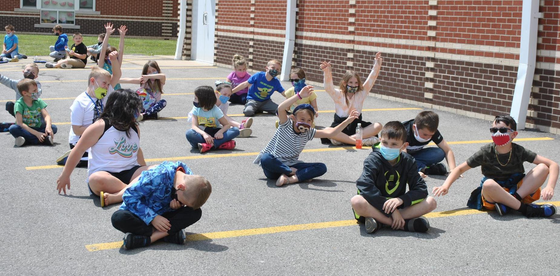 students sitting on pavement