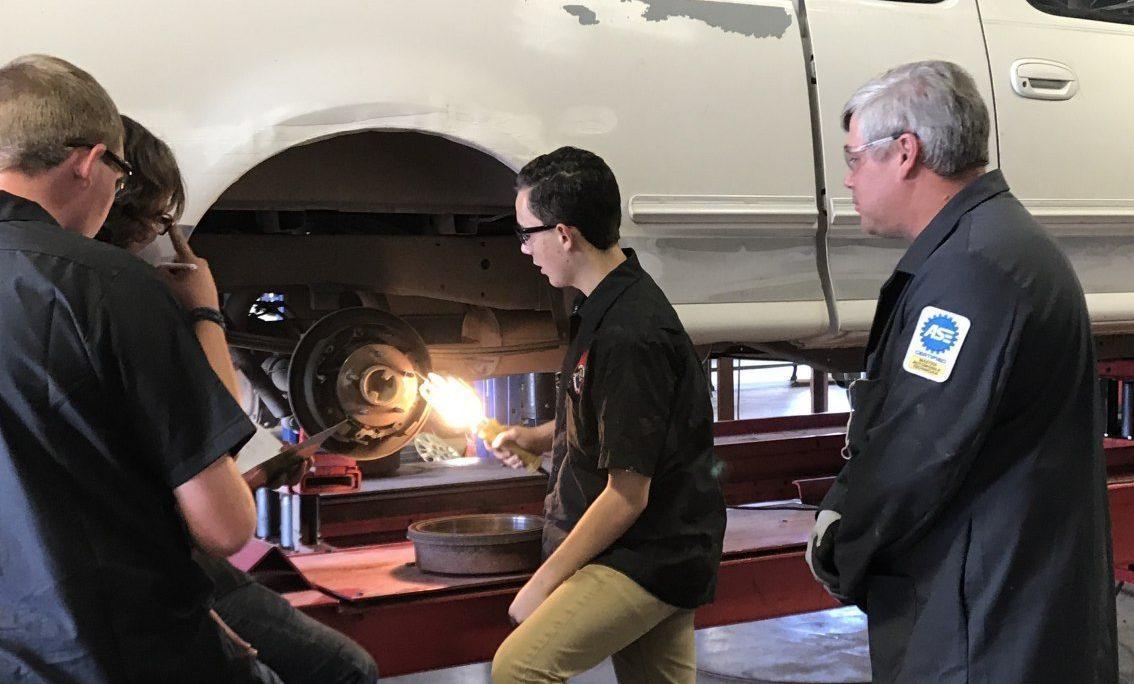 automotive students looking at car