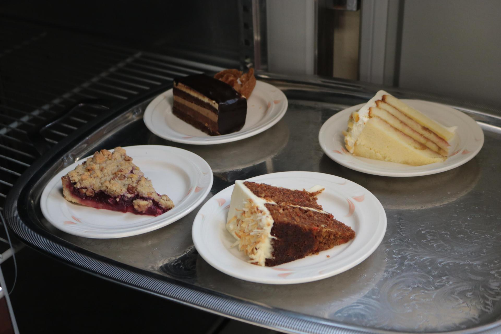 Four slices of cakes on plates