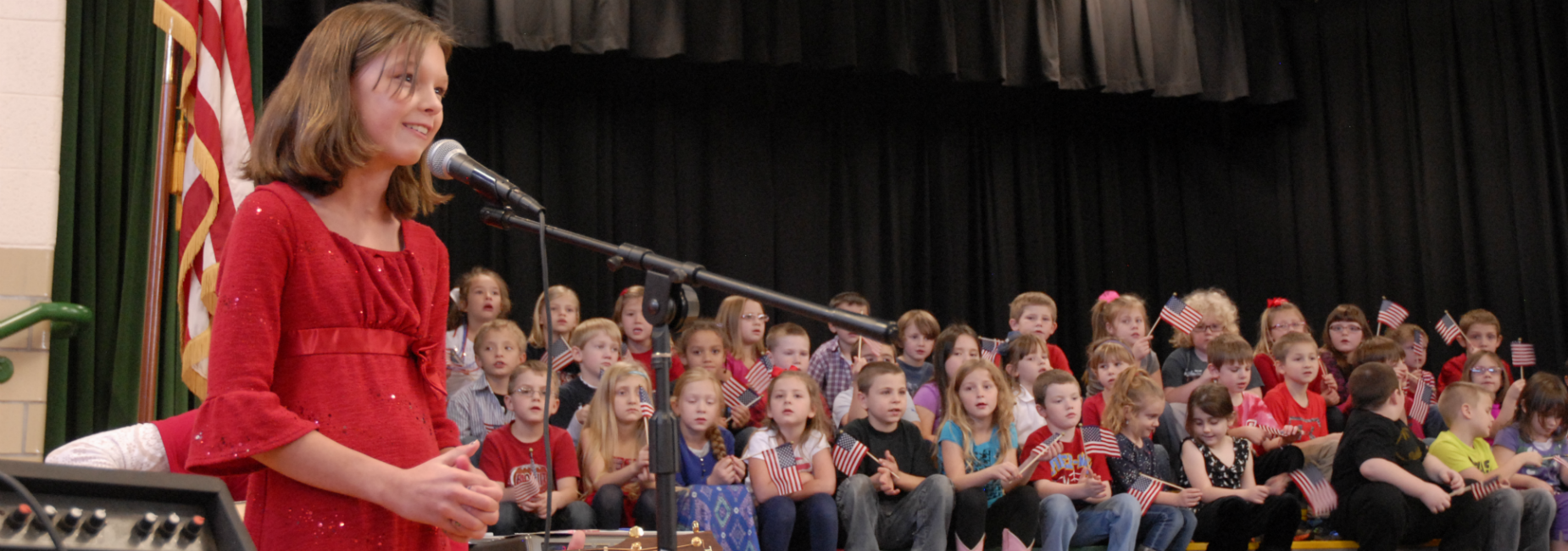 Fifth-grade girl singing during Sugar Grove Elementary School's Veterans Day assembly.