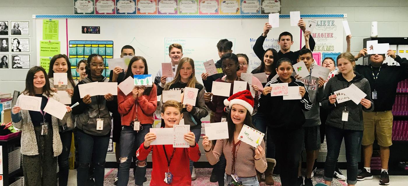 Students showing letters they wrote to wounded soldiers at Walter Reed Army Medical Center