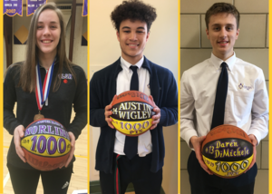 three students standing with painted basketball signifying they reached 1000 points in their high school career