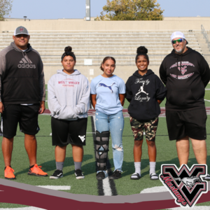 Vanessa Ledbetter, Ciara Green, and Lyric Jones standing with their coaches on the football field