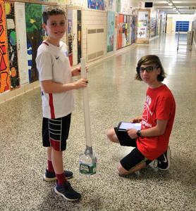 STEM volunteer helps camper tune musical instrument built out of recycled materials during STEM Camp.
