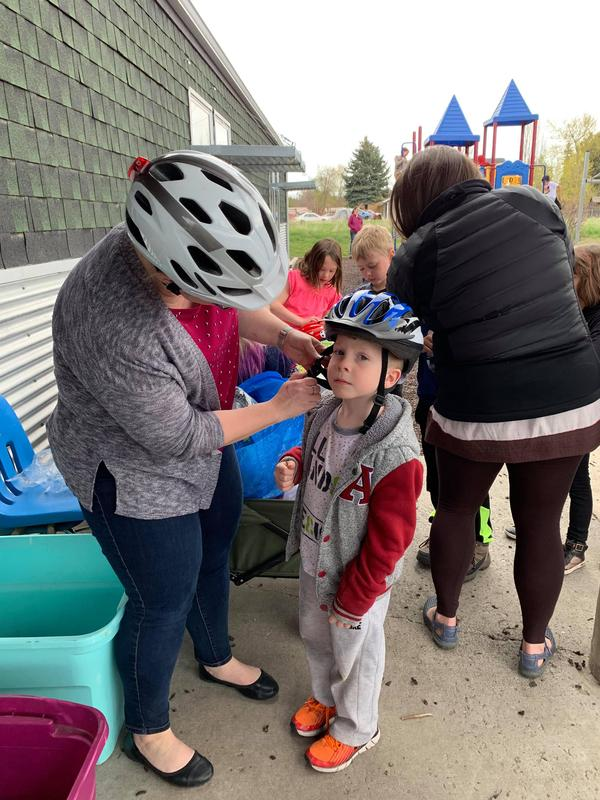 Kindergarten student being fitted for a bike helmet