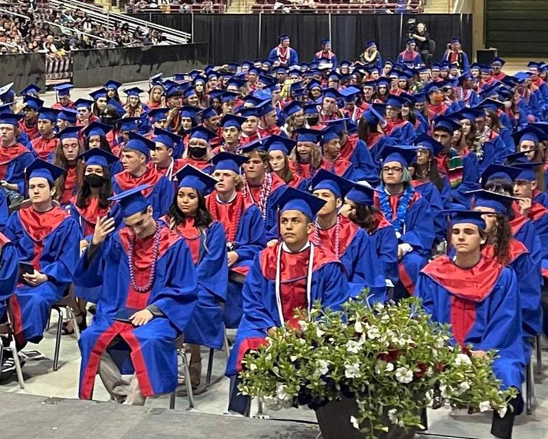 Nampa High students sit in their caps and gowns in the Ford Idaho Center arena.