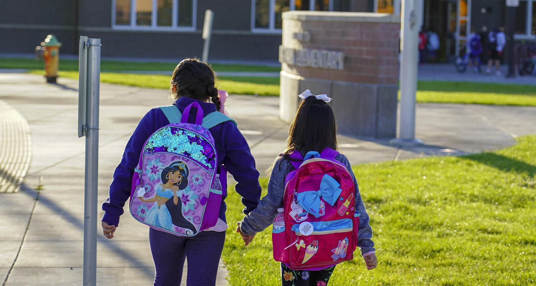 Two little girls holding hands while walking to school.