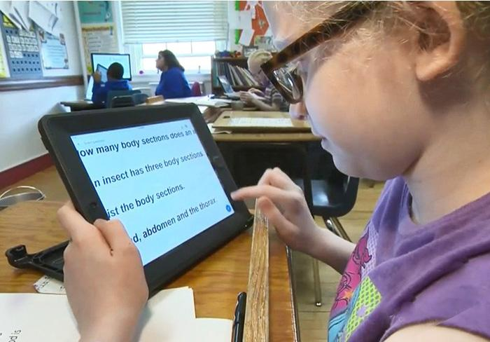 Low vision student using her iPad adapted for her vision loss