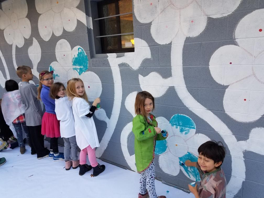 First graders paint the flower mural