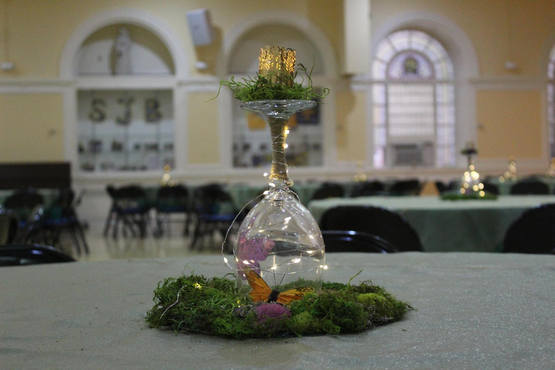 a table centerpiece of clear glass containing a monarch butterfly