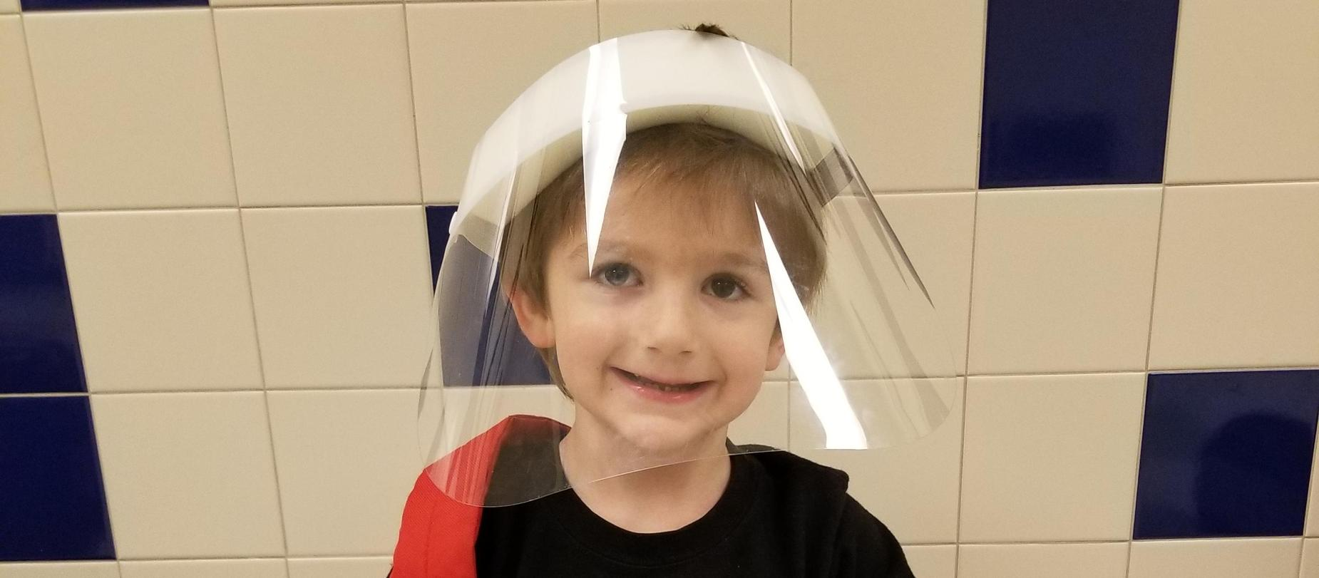 boy wearing face shield posing for the camera
