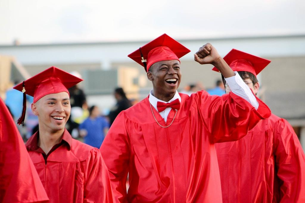 male victoria east graduate fist pumps and cheers to the crowd of family and friends in the stands