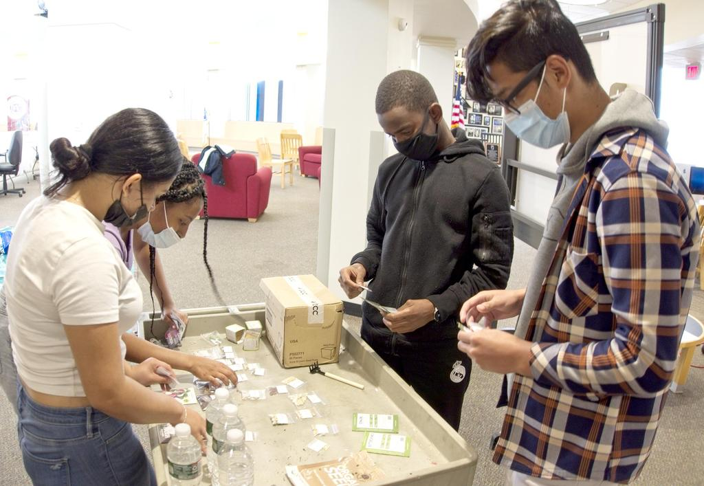 Students work around a table with gardening, planting and agriculture materials