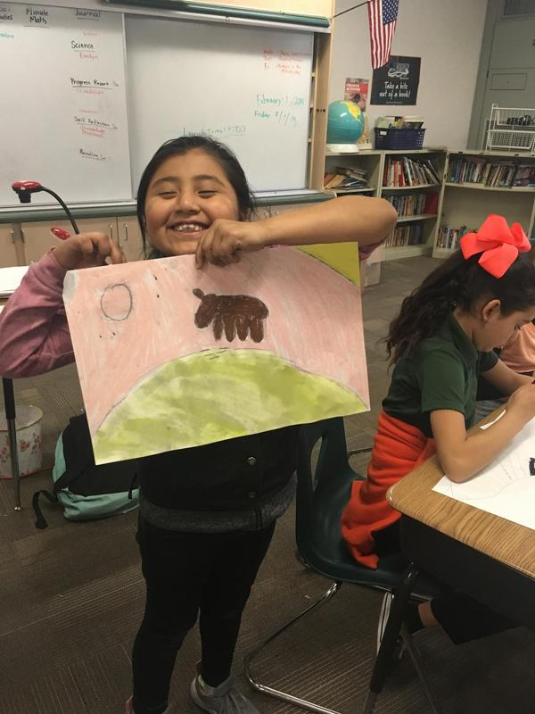 A student proudly shows her artwork