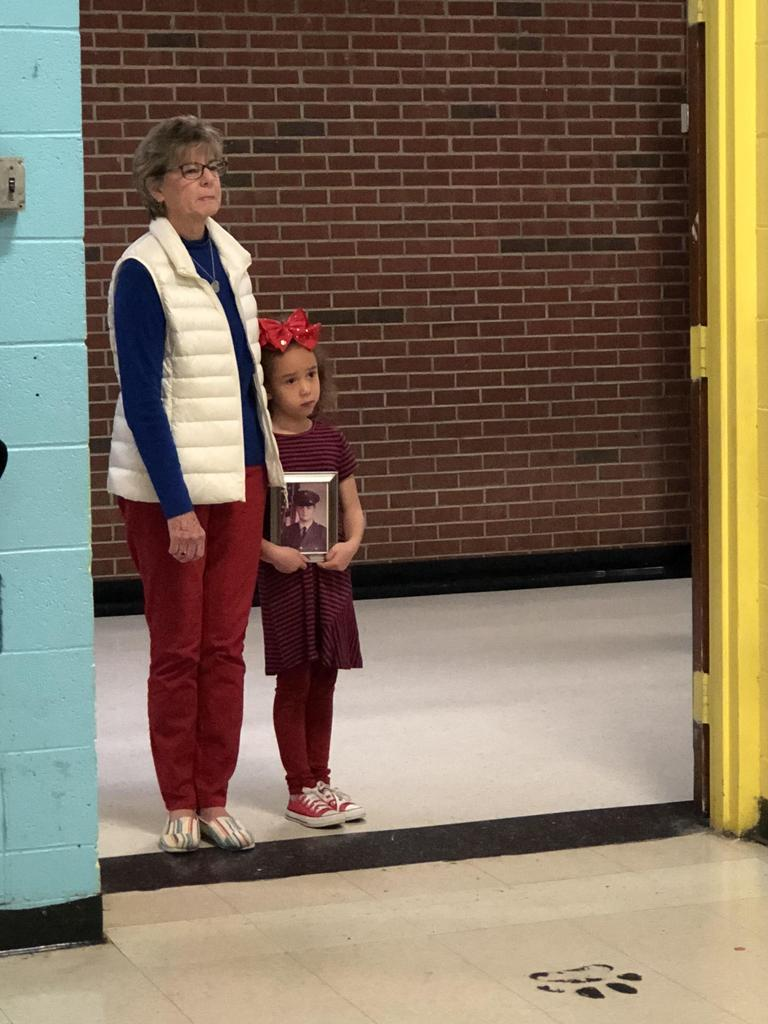 Veteran lady enters the gym with a young girl at the RCES Veterans Day assembly