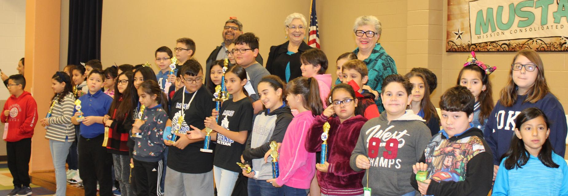 students with trophies and school board members