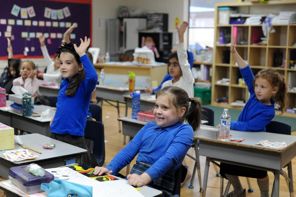 girls raising their hands to answer a question