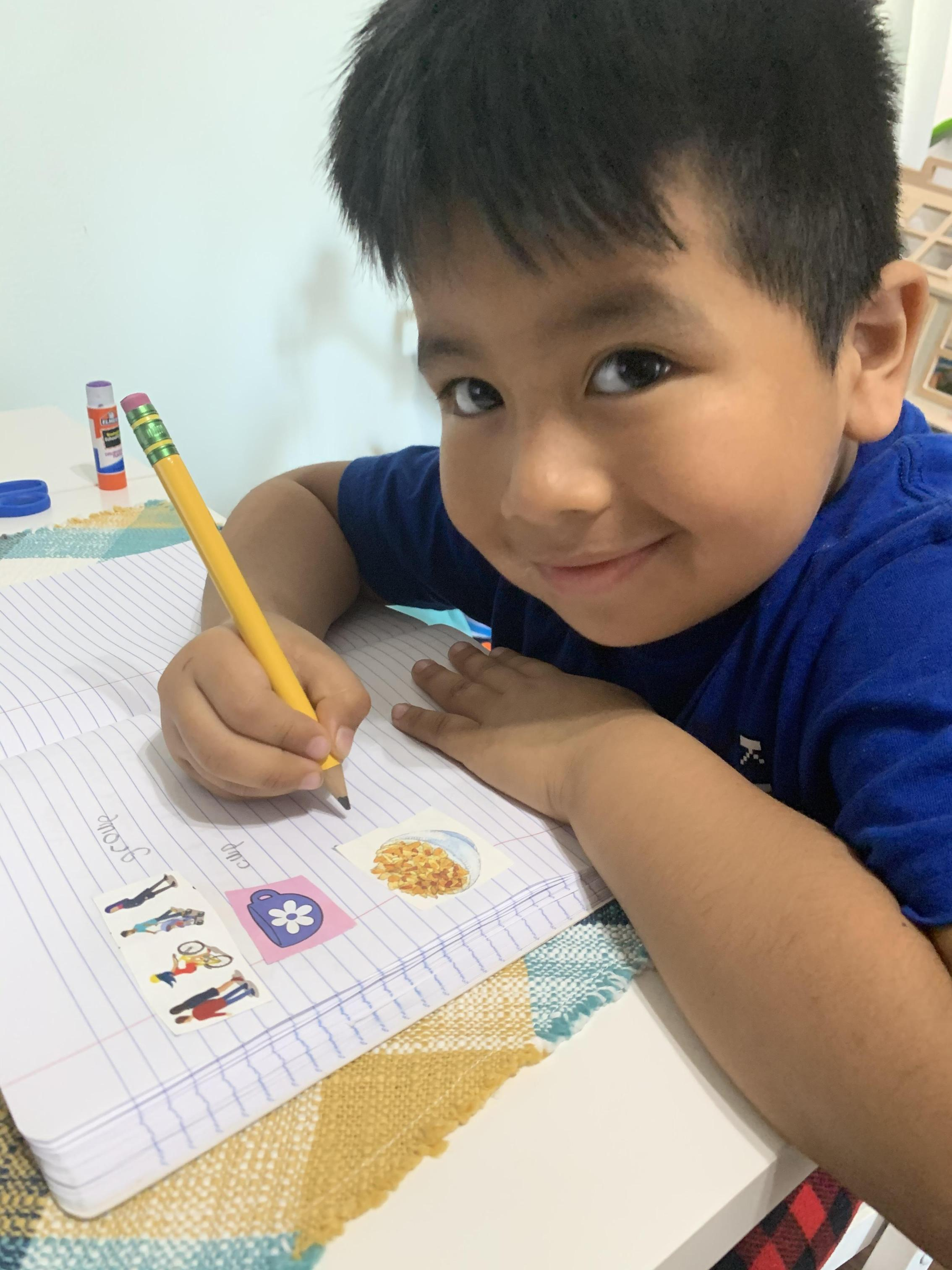 Kindergarten student at home during remote learning. He is writing and drawing in his class journal.