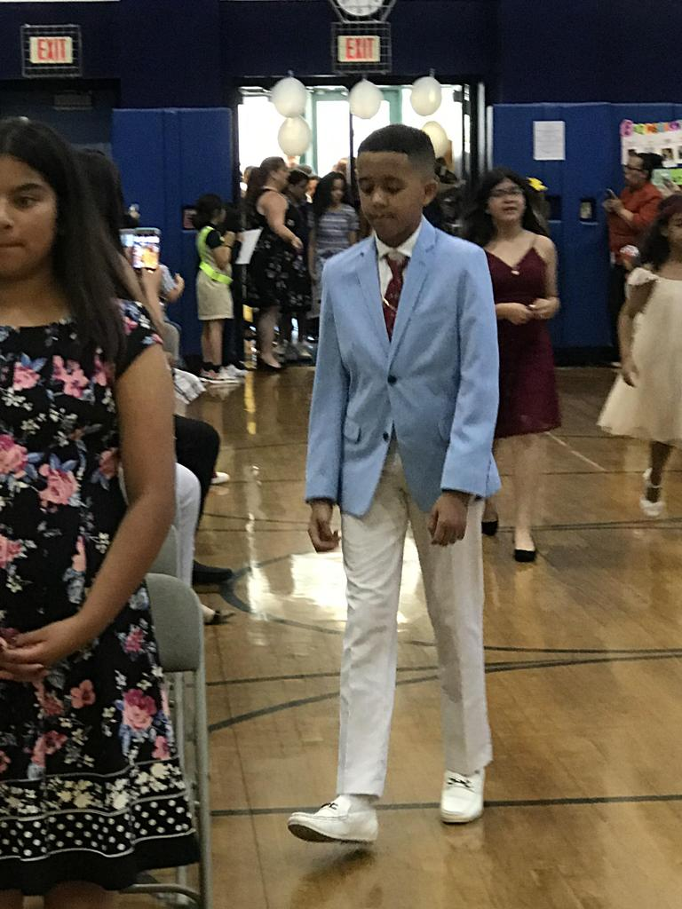 close up of boy in suit walking in