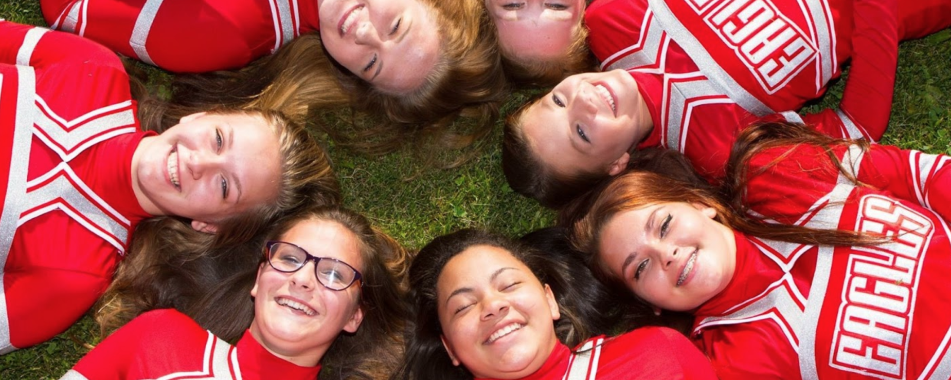 Cheerleaders lying in a circle, heads touching, smiling up at the camera