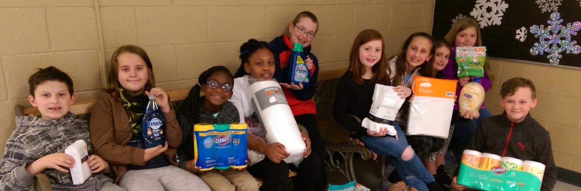 Photo of junior beta club students at South Columbia Elementary School, holding supplies like paper towels, towels, toilet paper, laundry detergent and other items they collected to donate to the Ronald McDonald House.