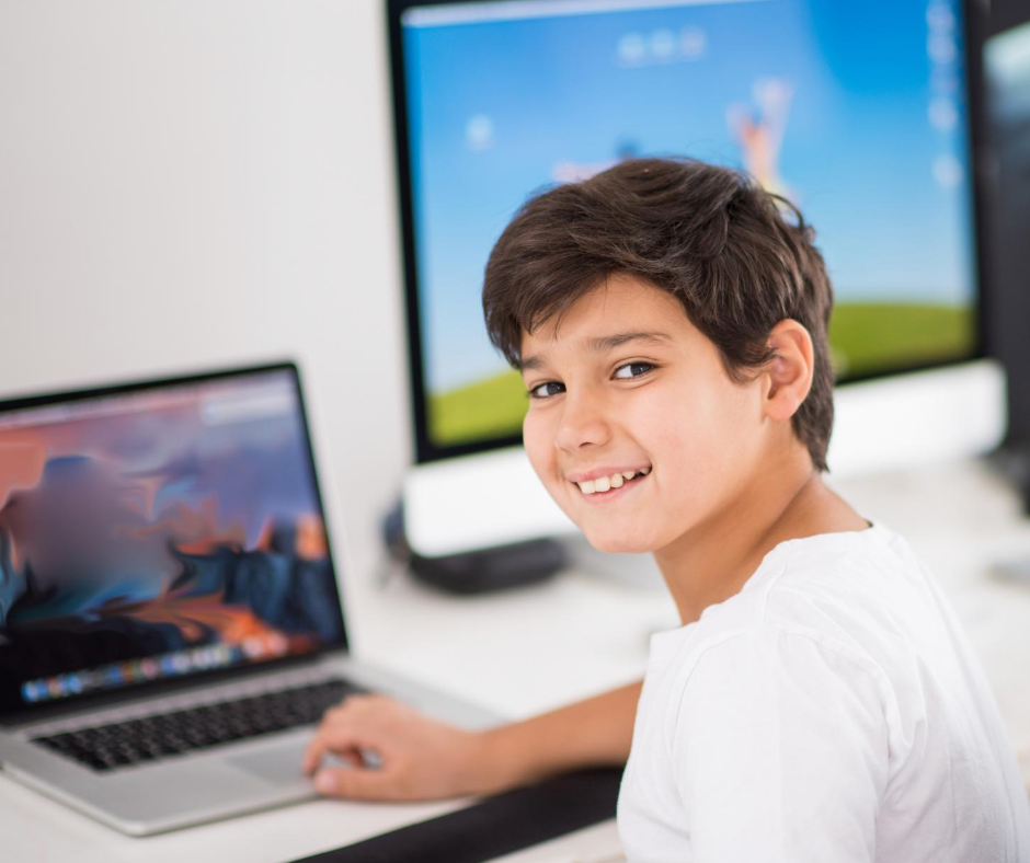 boy in front of two computers