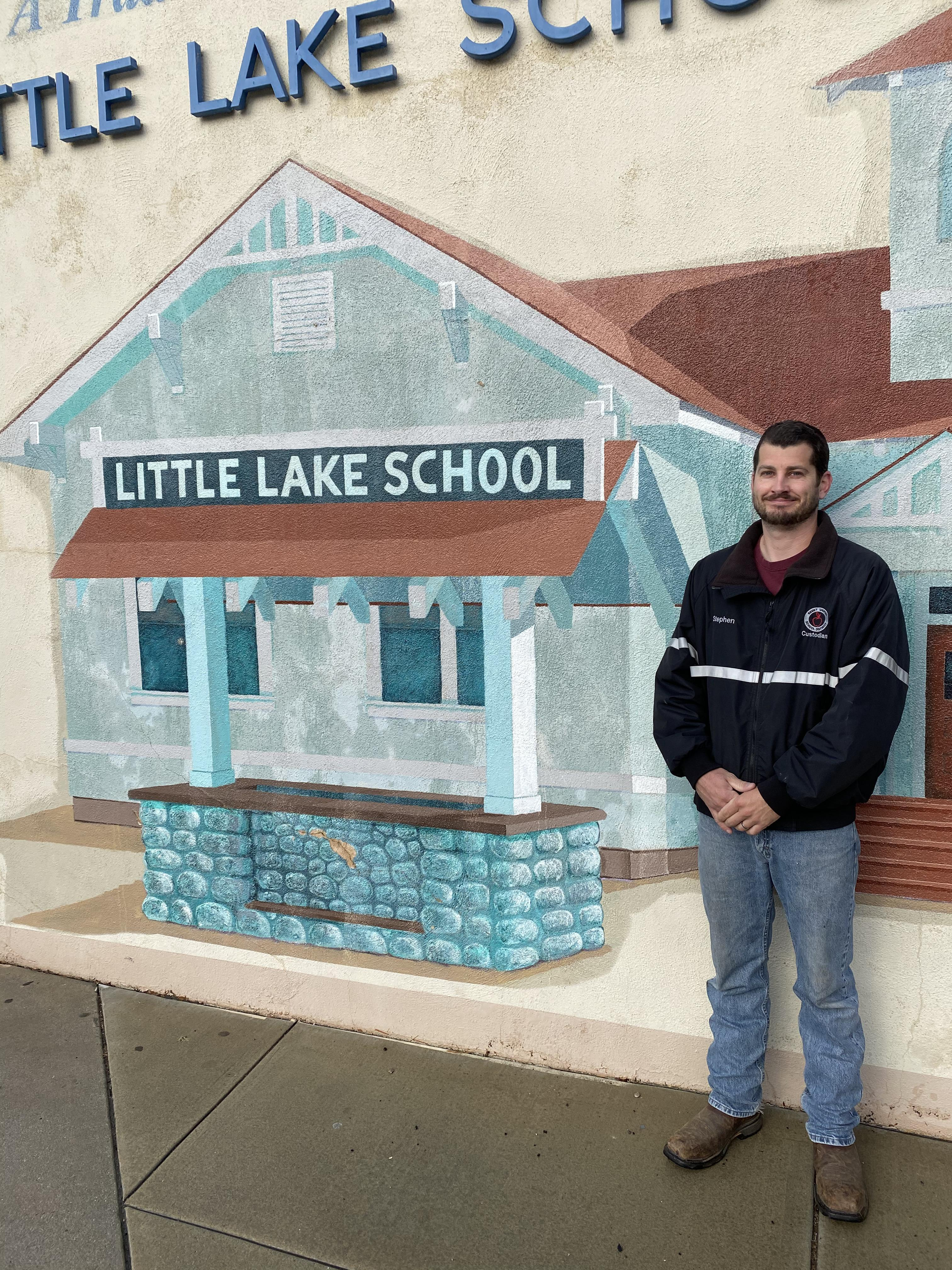 Stephen Heathcoat standing in front of the Little Lake mural.