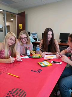 Picture of students drawing posters for the party