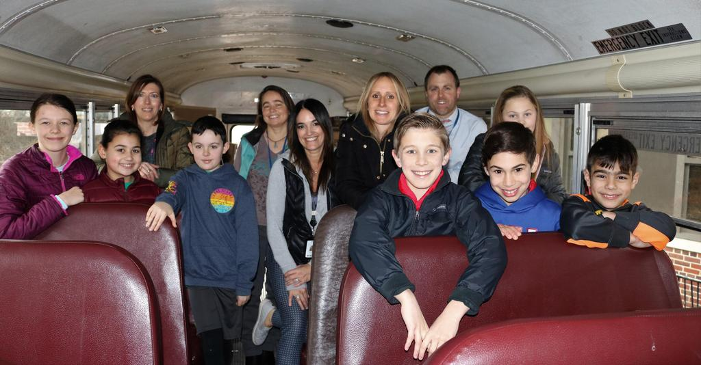 Photo of members of Franklin student government and staff on bus before heading to Newark to donate boxes of toys.