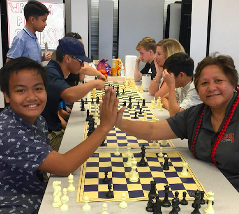 Students playing chess at a table with the principal and one student giving each other a high five