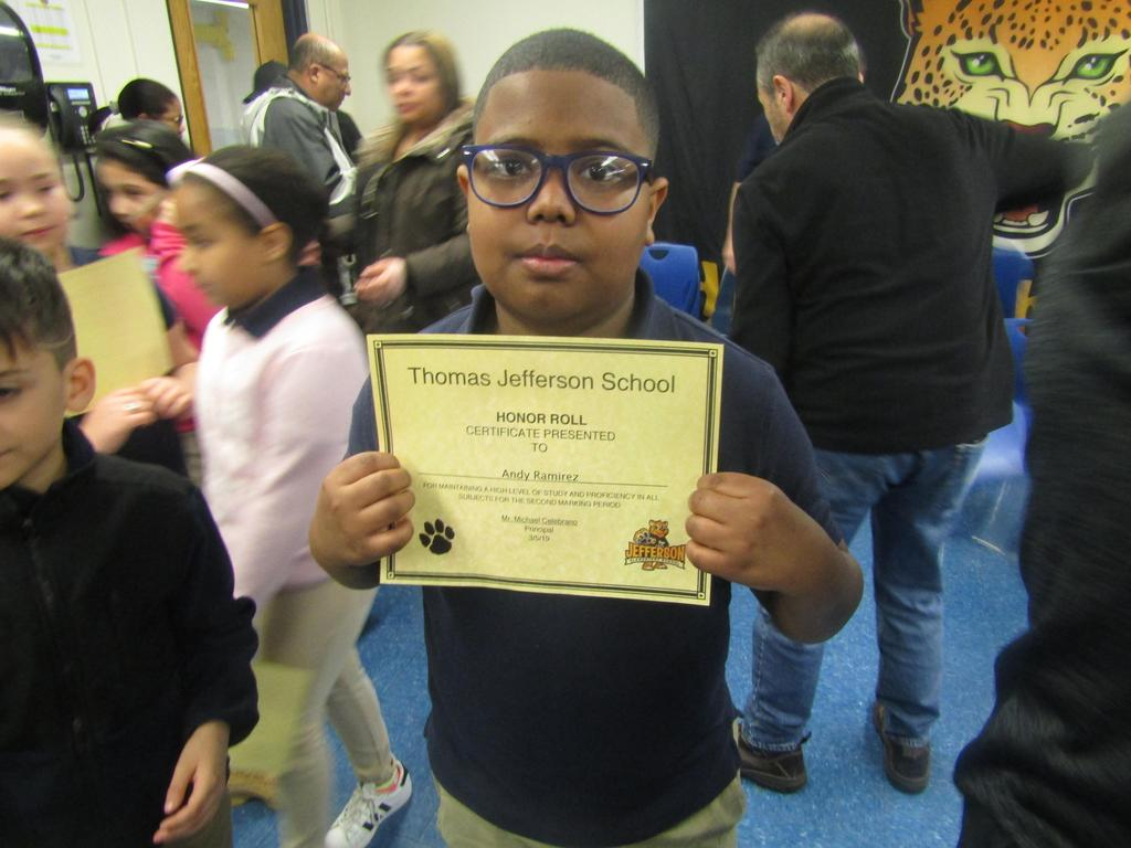 boy with glasses showing off his certificate