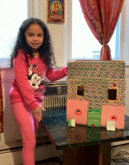girl showing off her box doll house