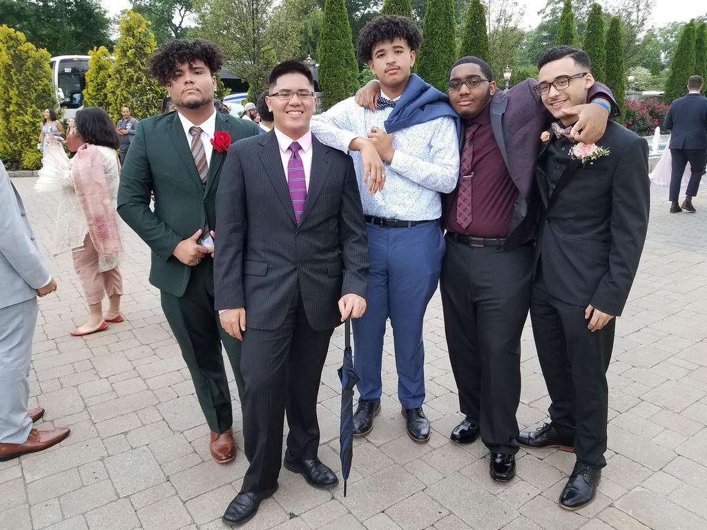 five students in suits smiling
