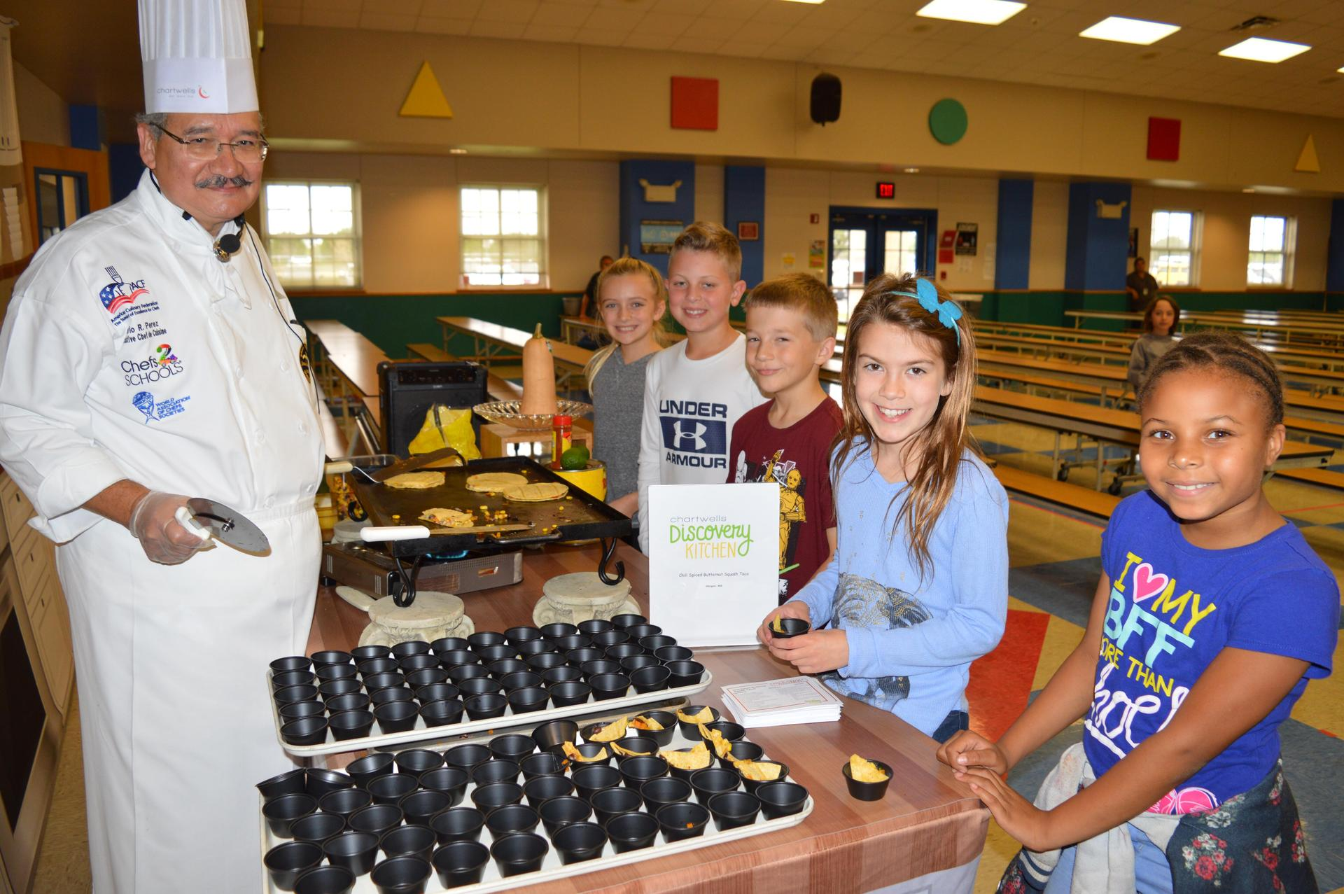 Chef Mario smiling with students.