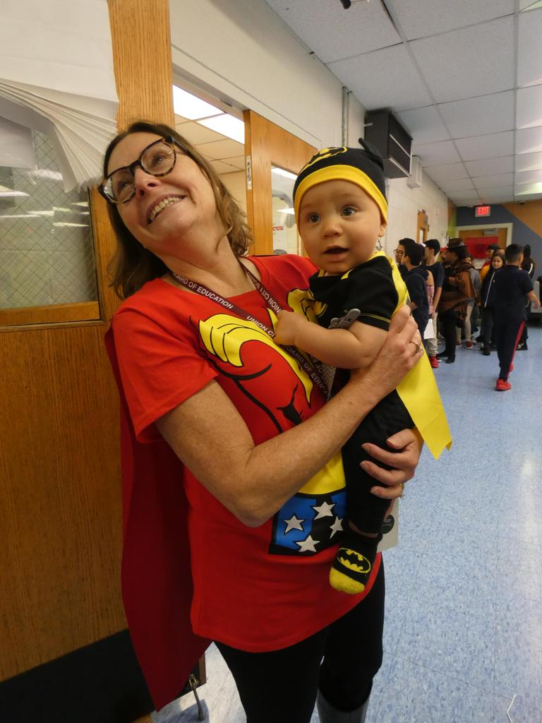 Principal Mrs. Dickson with baby dressed as batman