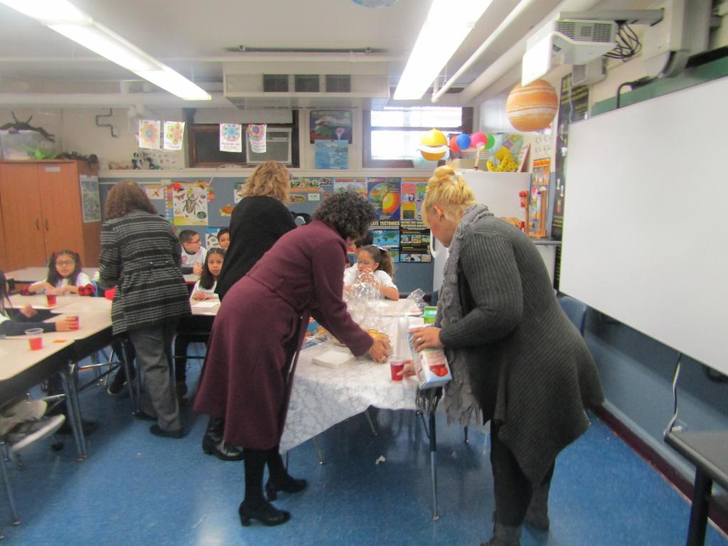teachers serving orange juice to students