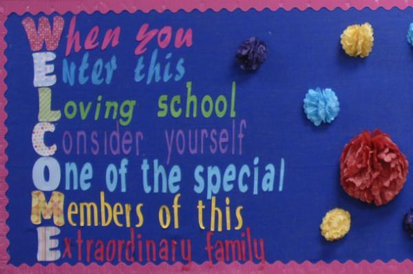 School school board reading When You Enter This Loving School, Consider Yourself One of the Special Members of This Extraordinary Family.