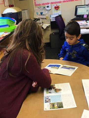 Mrs. Gutierrez  working with a small reading group.