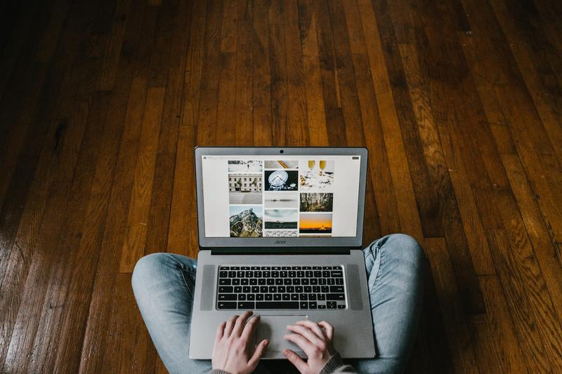 person sitting on a wooden floor using a laptop