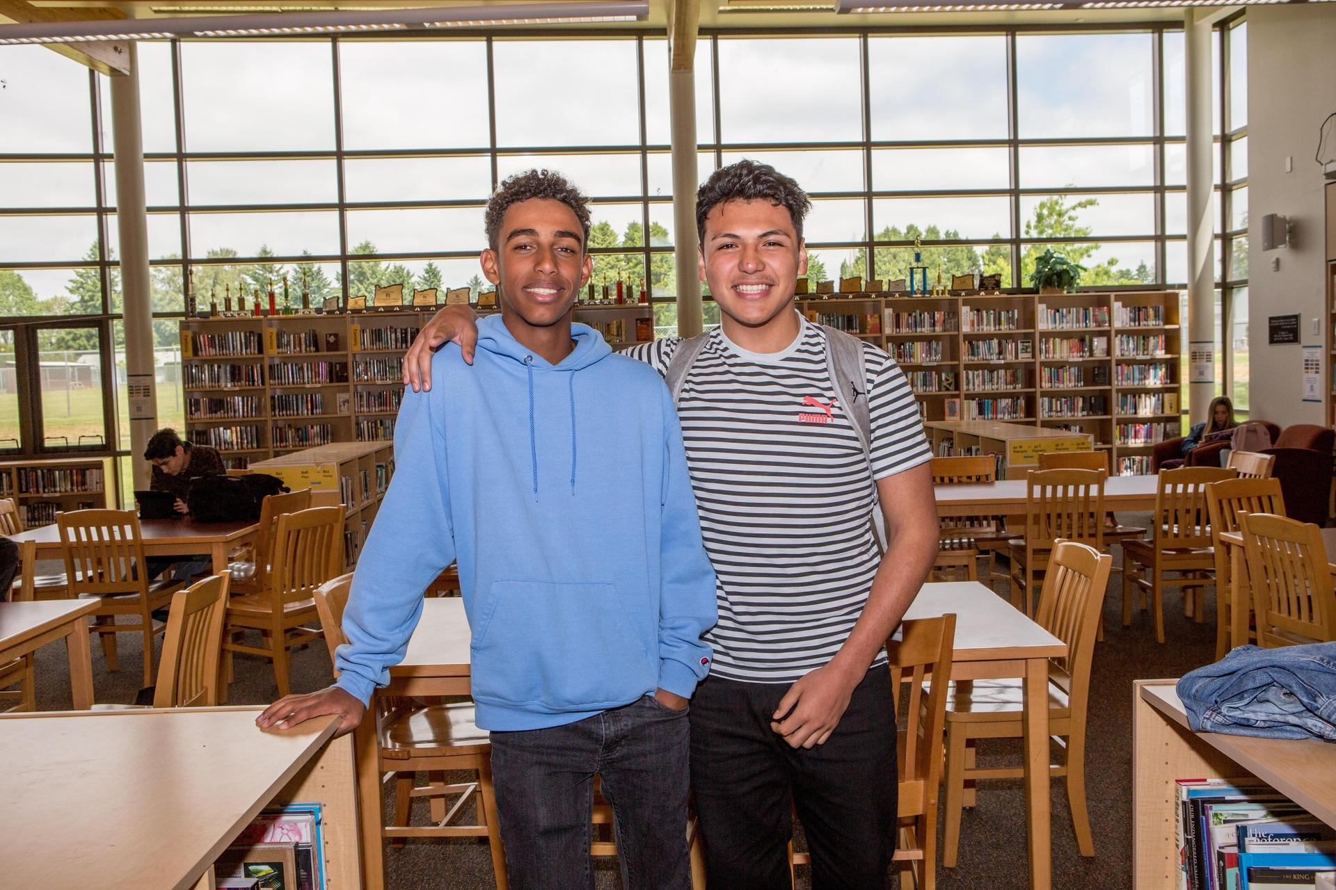 two students smiling in library