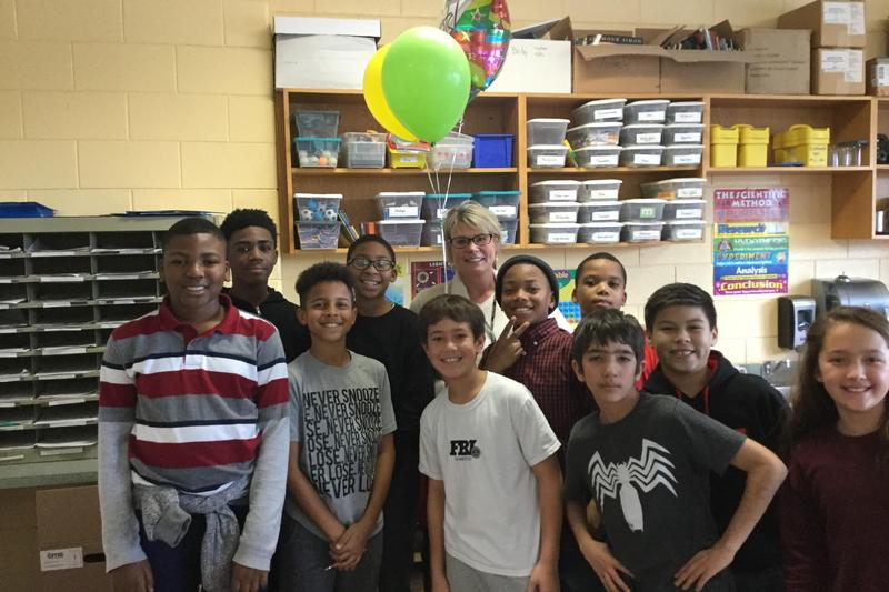 A photo of the 2018-2019 teacher of the year Mrs. Adams. She is holding balloons and surrounded by some 5th grade students after receiving the news that she won Teacher of the Year.