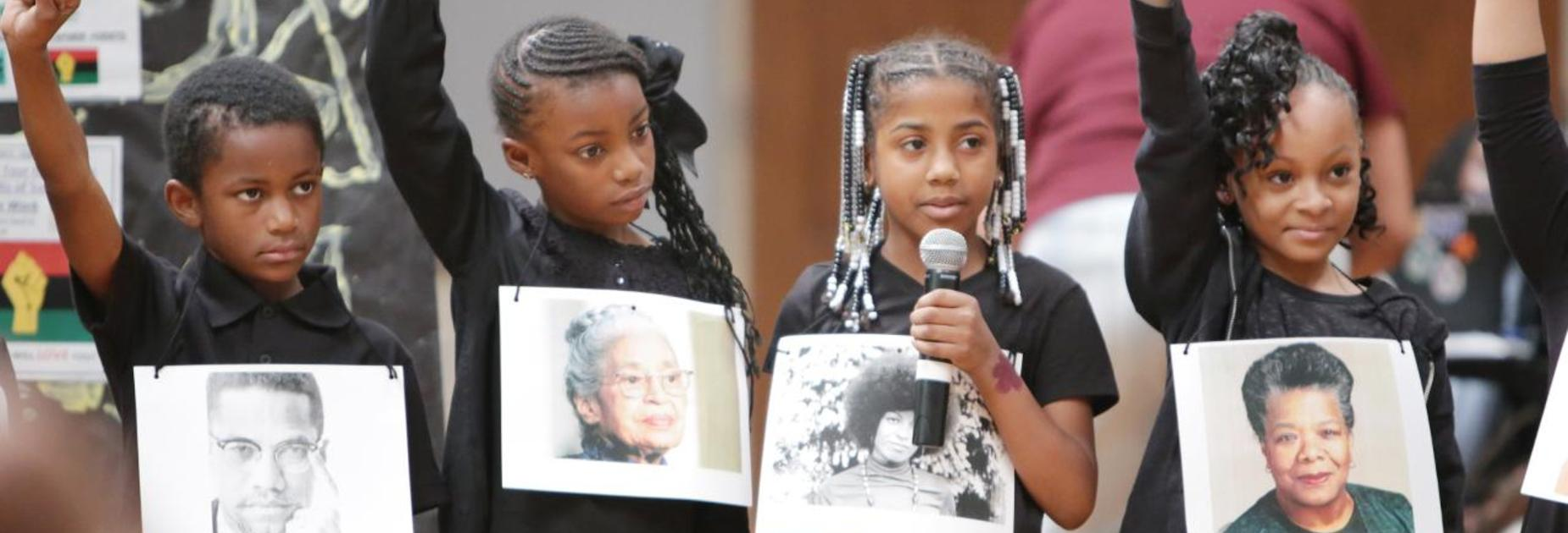 4 KLP students holding pictures of famous Black Americans